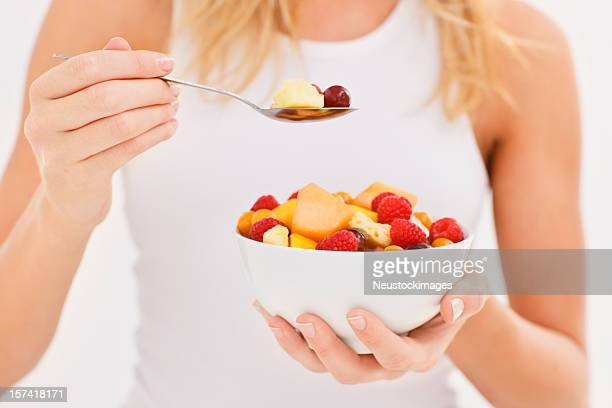 Woman eating fruit salad
