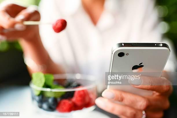 Woman 食べるフルーツのデザートで手で iPhone 4 S