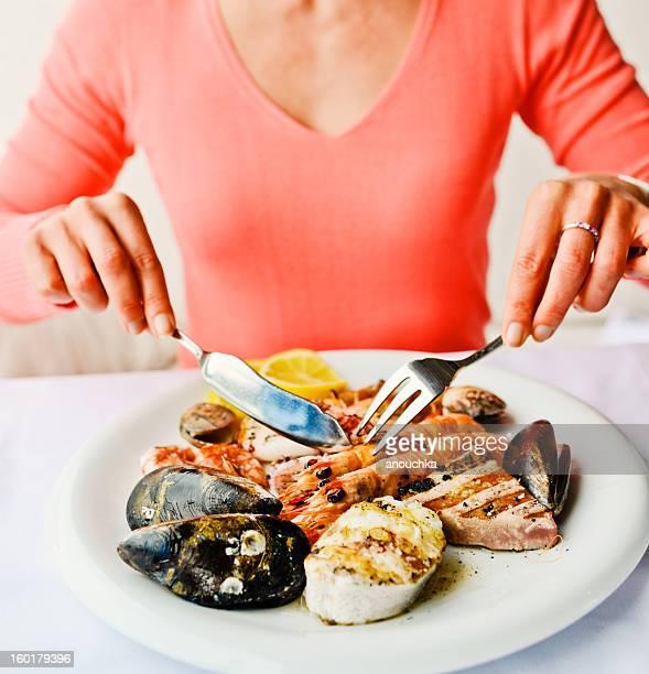 Femme manger dans un restaurant de fruits de mer grillés