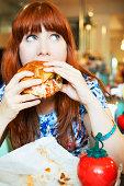 woman eating hamburger in cafe