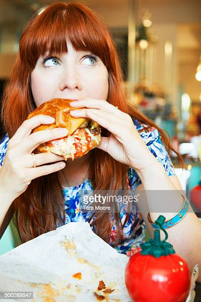 woman eating hamburger in cafe