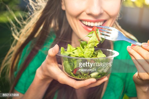 Woman eating healthy salad : Stock Photo