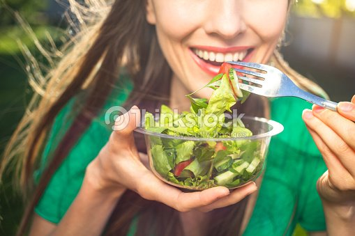 Woman eating healthy salad : Stock Photo