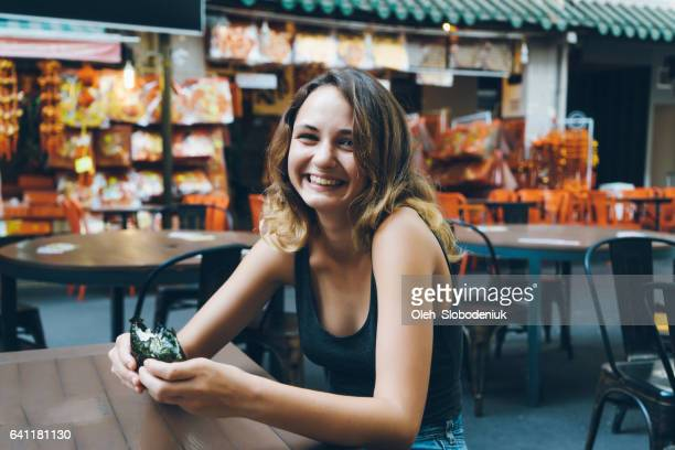 Woman eating in Chinatown district in Singapore