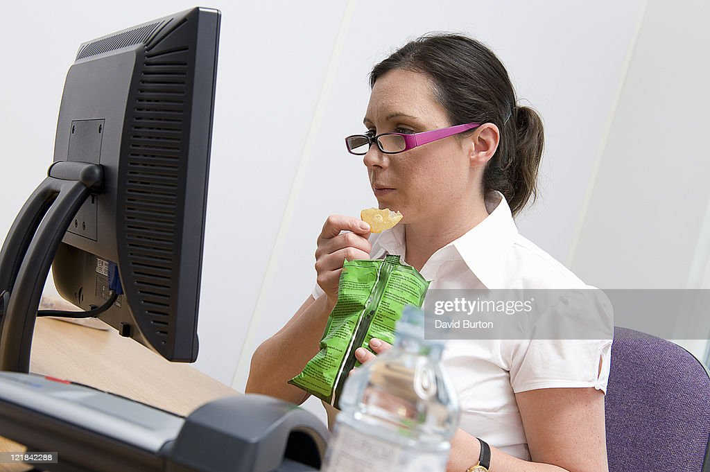 Woman eating lunch at work : Stock Photo