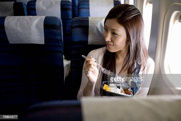 Woman eating meal in airplane