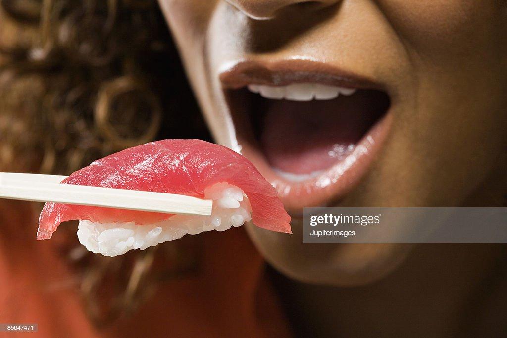 Woman eating nigiri sushi : Stock Photo