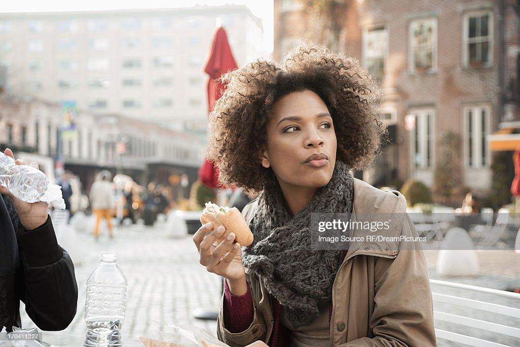 Woman eating on city street : Stock Photo
