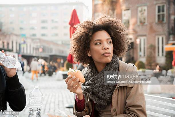 Woman eating on city street