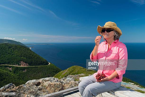 Woman eating on hiking trail, Skyline, Cabot trail, Cape Breton