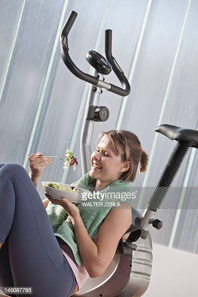 Woman eating salad by exercise machine