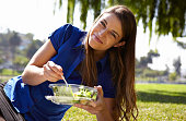 Woman eating salad in park