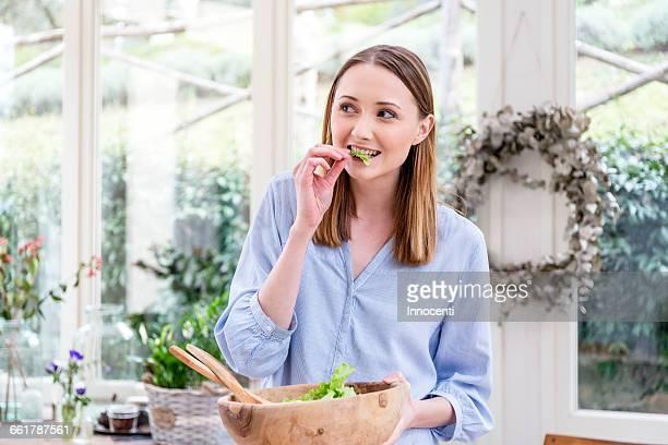 Woman eating salad leaves looking away