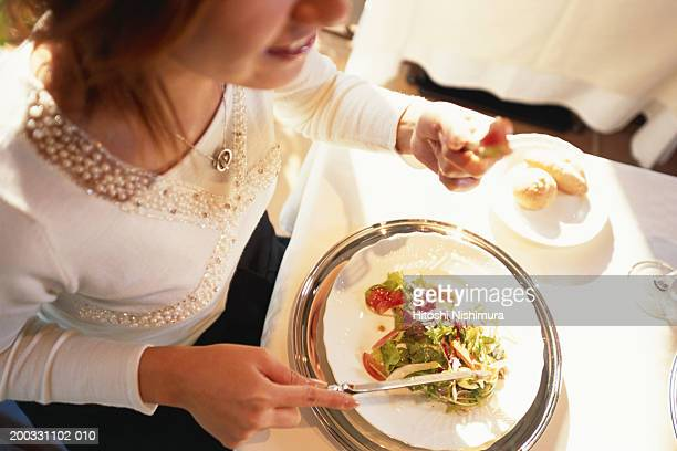 Woman eating salad, mid section, elevated view