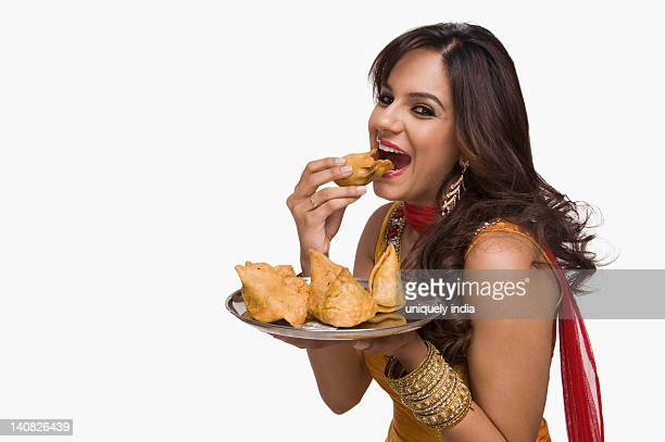 Woman eating samosa the traditional Indian snack