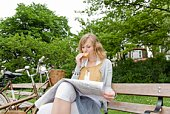 Woman eating sandwich on park bench