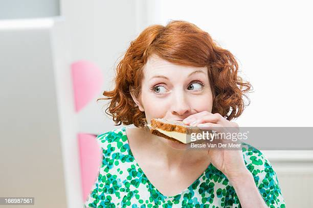 Woman eating sandwich while working on computer.
