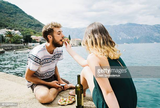 Woman eating sandwiches and drink wine at Kotor bay