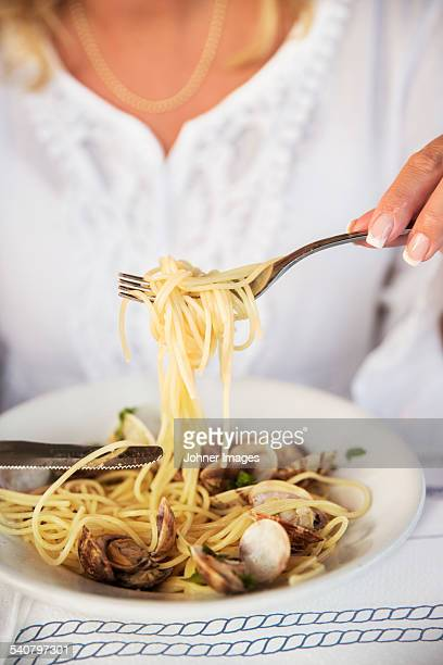 Woman eating seafood pasta