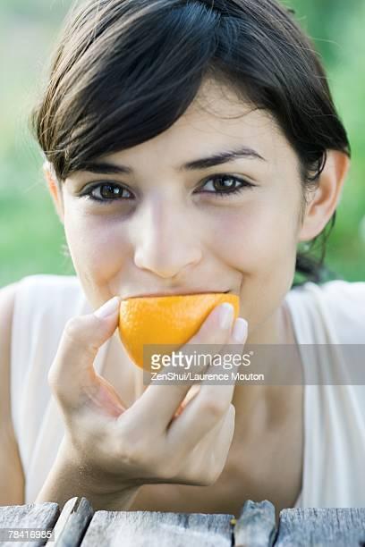Woman eating slice of orange, smiling at camera, close-up