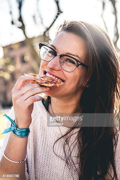Donna mangia la fetta di pizza