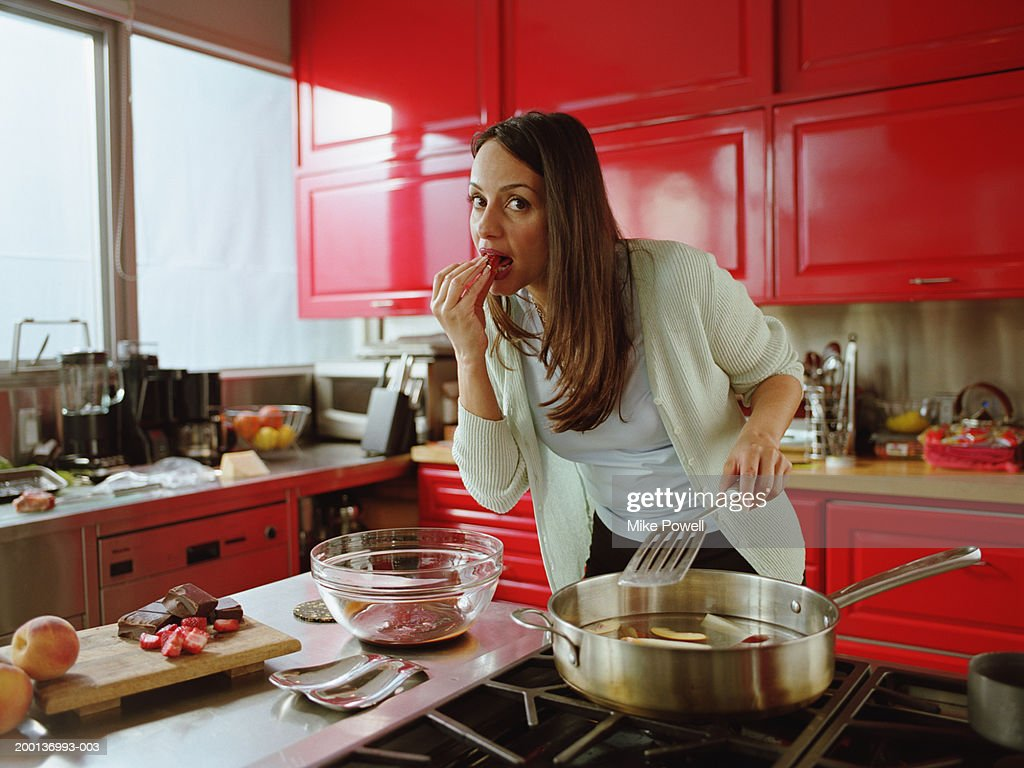 Woman eating strawberry while cooking in kitchen : Stock Photo