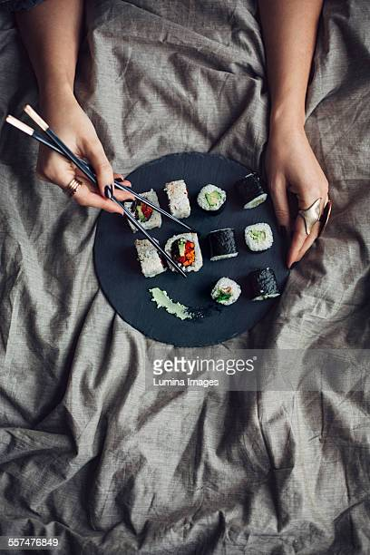 Woman eating sushi with chopsticks in bed