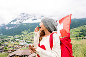 Young woman with swiss flag eating chocolate outdoors in the mountains. Having great vacations in Switzerland