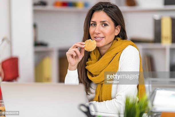 Woman eating tasty cookie