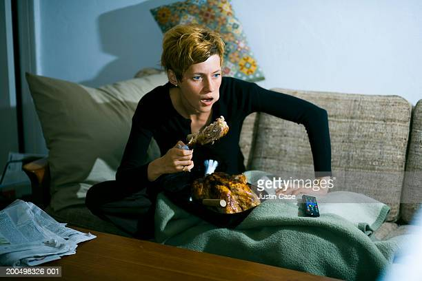 Woman eating turkey on couch