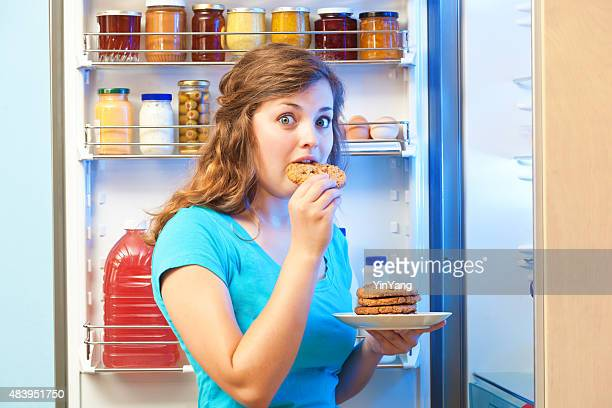 Woman Eating Unhealthy Cookie Desert in Front of Open Refrigerator