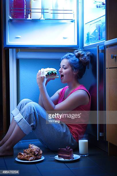 Woman Eating Unhealthy Midnight Snack late Night Under Open Refrigerator