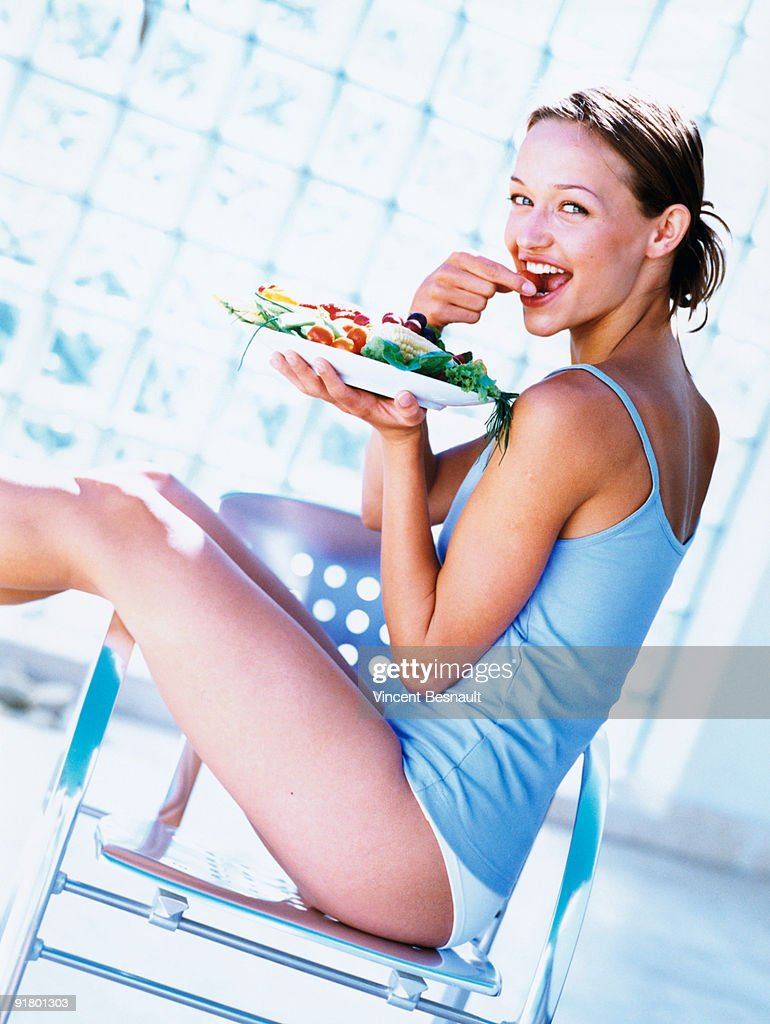 Woman eating vegetables : Stock Photo