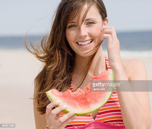 Woman eating watermelon at beach
