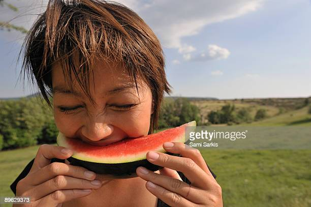 Woman eating watermelon, outdoors