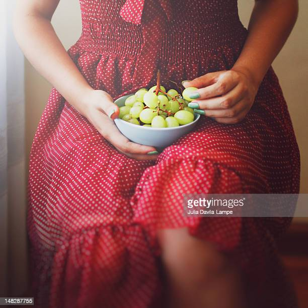 Woman eating white table grapes