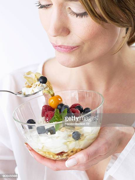 Woman eating yoghurt muesli with fruit, close up