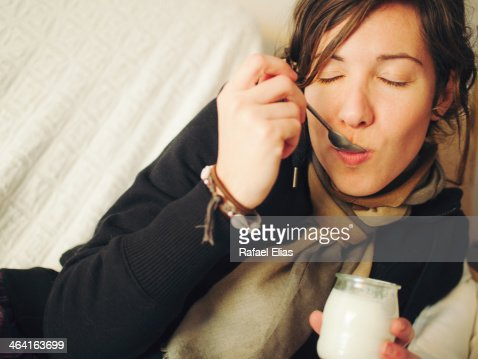 Woman eating yogurt : Stock Photo