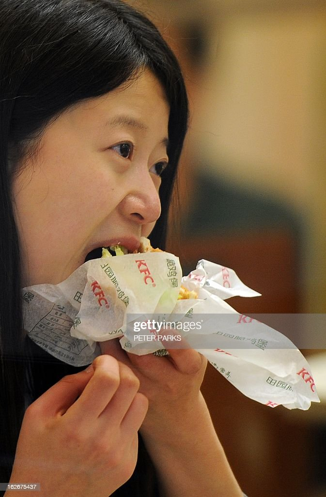 A woman eats a chicken burger in a branch of a KFC restaurant in Shanghai on February 26, 2013. The fast food giant has cut more than 1,000 farms from its supplier network in China to ensure food safety after a scandal over tainted chicken hurt sales in the key market last year. AFP PHOTO/Peter PARKS