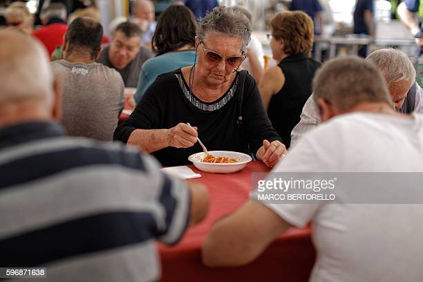 A woman eats a dish of spaghetti all'amatriciana during a charity event in Piazza San Carlo in Turin on August 28 whose profits are to help the...