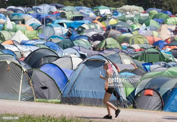 A woman eats a ice lolly as she passes recently erected tents as temperatures reach record levels at the Glastonbury Festival at Worthy Farm in...