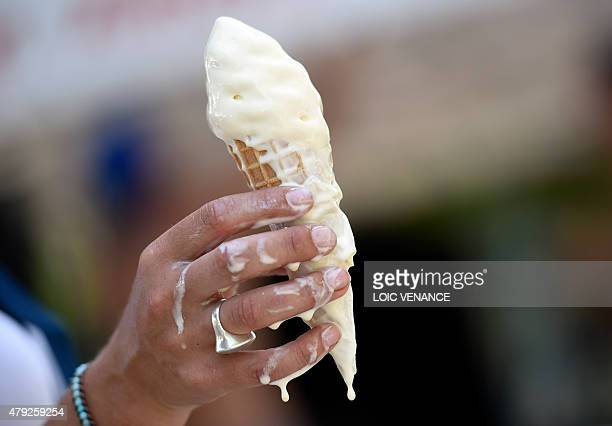 A woman eats a melting ice cream on July 2 2015 in Paris AFP PHOTO / LOIC VENANCE / AFP / LOIC VENANCE