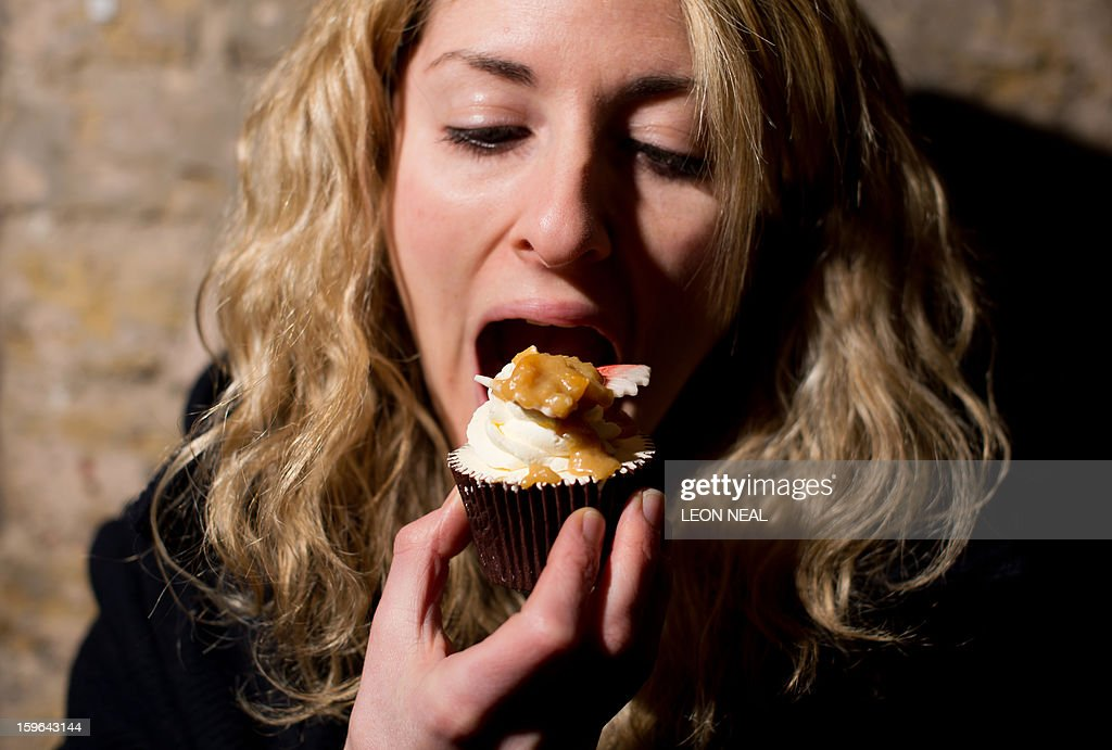 A woman eats a 'Vomit cupcake' made from entirely edible ingredients at a film set pop-up experience in east London on January 17, 2013. The event was held to promote the release of a new horror film 'The Helpers'.