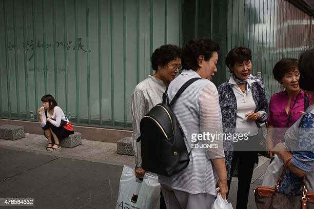 A woman eats an ice cream as others talk amongst themselves on a shopping street in Seoul on June 26 2015 South Korea on June 25 announced a 14...