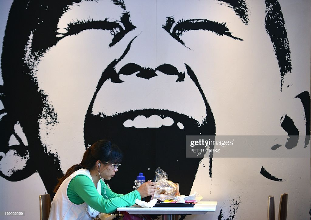 A woman eats at a fast food restaurant in Shanghai on May 22, 2013. China's top court recently announced its first ever detailed guidelines for the punishment of food-safety related crimes after a string of complaints including supplying meat from animals which died of illness, selling food with excessive amounts of chemical additives, and falsely advertising food products, the report said, citing China's Supreme People's Court. AFP PHOTO/Peter PARKS
