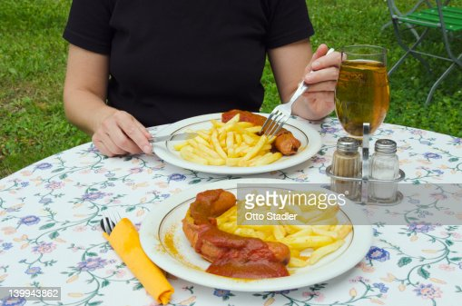 Woman eats curry sausage with French fries : Stock Photo