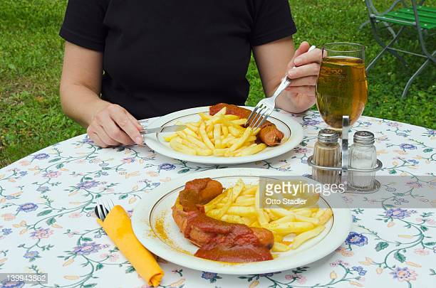 Woman eats curry sausage with French fries