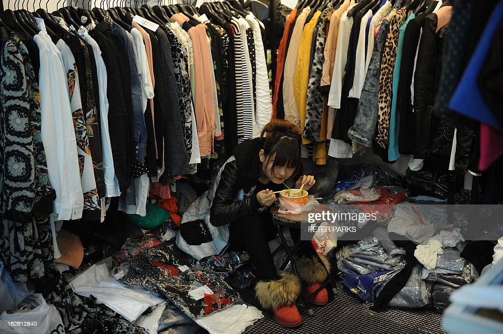 A woman eats her lunch in a shop in a wholesale clothing market in Shanghai on February 25, 2013. China's manufacturing growth hit a four-month low in February but remained positive, British banking giant HSBC said on February 25, noting that the world's second-biggest economy was still recovering slowly. AFP PHOTO/Peter PARKS