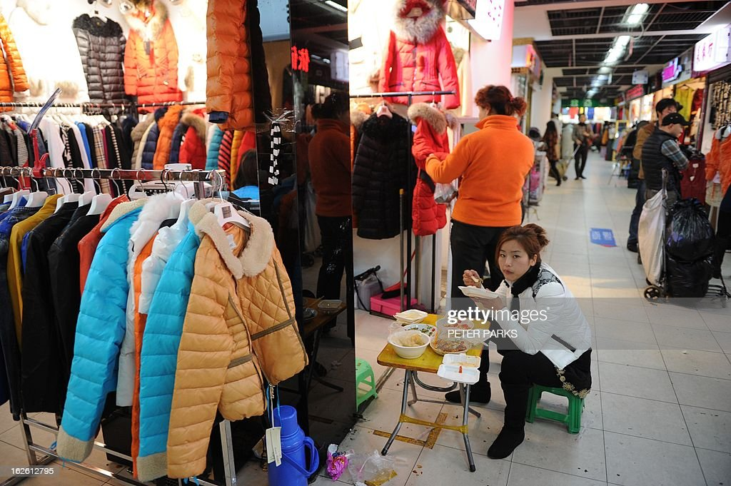 A woman eats her lunch outside a shop in a wholesale clothing market in Shanghai on February 25, 2013. China's manufacturing growth hit a four-month low in February but remained positive, British banking giant HSBC said on February 25, noting that the world's second-biggest economy was still recovering slowly. AFP PHOTO/Peter PARKS