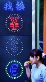 A woman eats in front of a currency exchange sign in Hong Kong on September 15 2011 Hong Kong said it has no plans to unpeg its currency from the US...